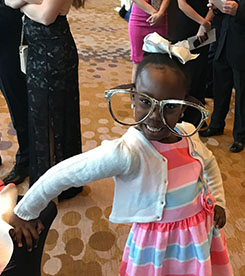 Little girl wearing humorously large glasses