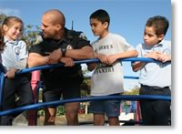 Photo of police officer interacting with 3 young children.