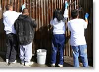 Photo of teenage kids painting a fence.