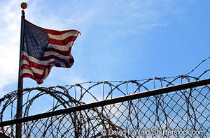 a picture of an American flag waving over a barbed wire fence