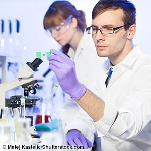 A man wearing gloves and a lab coat and looking at a microscope slide in a science lab. A woman is in the background.