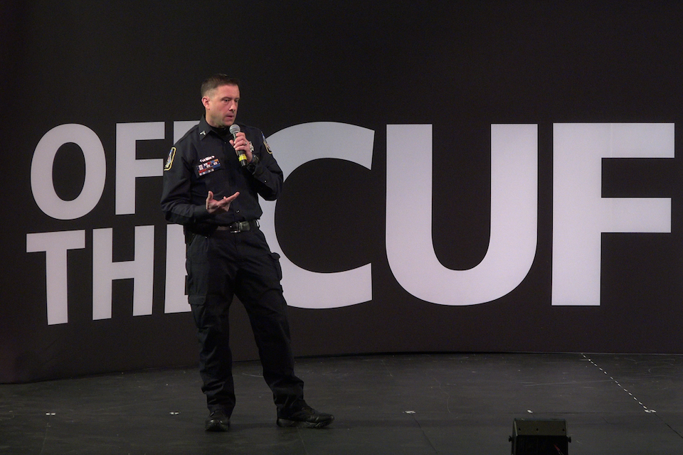 Policeman on stage talking in a microphone